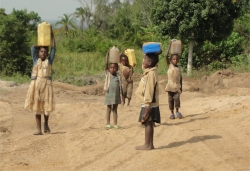 Children from the village walk for miles to collect water on the Land Sand Mining bore hole.
