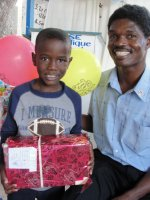 Seen here a little boy with Pastor Bannes the Kids' Evangelism Explosion Haiti Director receiving his gift.