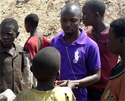 Pastor Abraham, seen here in the centre of the street children on one of the rubbish dumps in Kampala