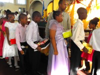 Seen here at their Harvest Festival bearing their Make Jesus Smile shoebox gifts as they brought them to the alter to 'Sow a seed of Love' for Haiti.