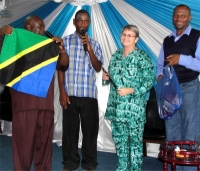 Jenny receiving her gifts including a flag of Tanzania from Bishop and Pastor David and the KIMI Dar Es Salaam coordinator - Pastor Imanuel Mwamakola seen here on the right.