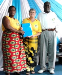 Bishop and his wife receiving their Zambia Master Copies of the KIMI curriculum, being presented by Jenny Tryhane their KIMI Leadership trainer.