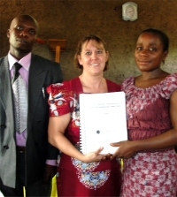 Seen here with his wife receiving his KIMI curriculum and manual from Pastor Laura the KIMI Africa Representative.